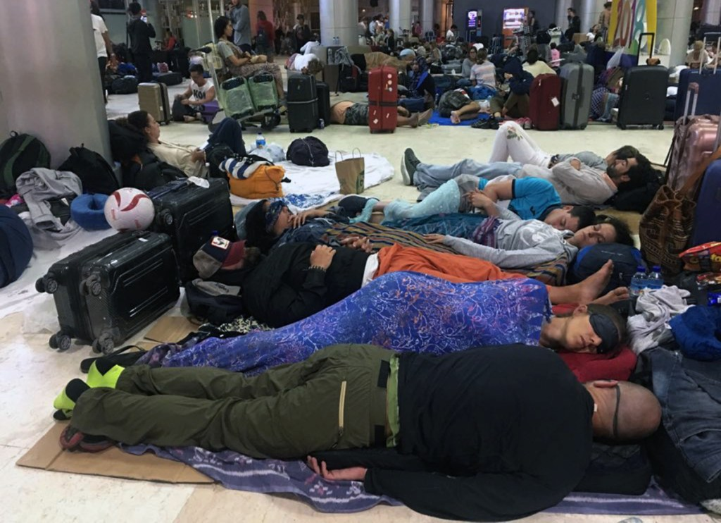 Foreign tourists sleep on the floor as they are stranded at Lombok International Airport following an earthquake in Praya, Lombok Island, Indonesia, Monday, Aug. 6, 2018. The powerful earthquake flattened houses and toppled bridges on the Indonesian tourist island of Lombok, killing a large number of people and shaking neighboring Bali, as authorities said that rescuers still hadn't reached some devastated areas and the death toll would climb. (AP Photo/Niniek Karmini)