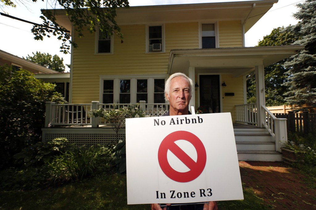 Tom Sidar of Bradley Street holds a lawn sign in August calling for an end to short-term rentals in residential zones.