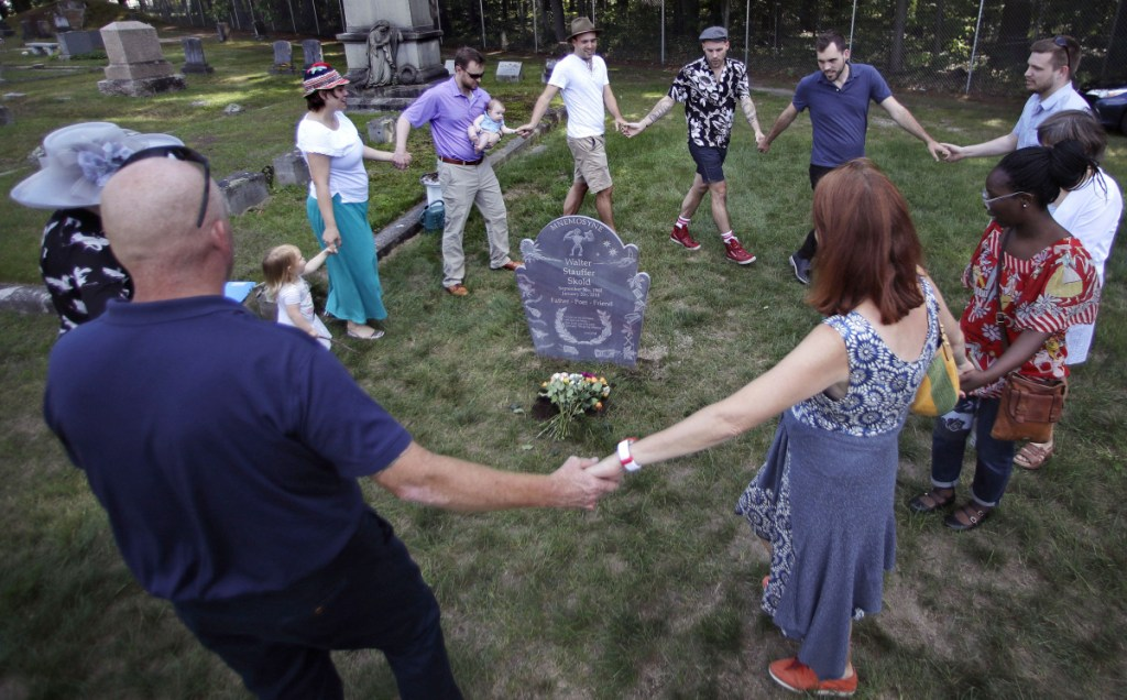 The family of Walter Skold, founder of the Dead Poets Society of America, dance and sing around his grave at Pine Grove Cemetery in Brunswick on Monday. Skold died of a heart attack after enlisting the son of novelist John Updike to carve a unique grave marker.