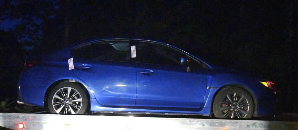 A car, operated by a man who committed suicide after being police conducted a traffic stop, is towed away Thursday night from Timberwood Drive in Gardiner. A body was discovered in the trunk of the car, a blue Sabaru with Massachusetts license plates, police said.