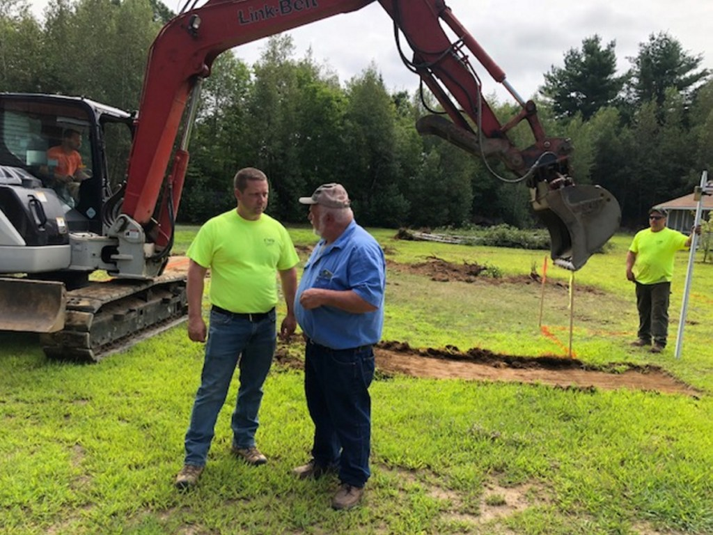 Mickey Wing, right, of Central Maine Disposal and Excavation, confers with Joel Violette, of Fairfield Drafting & Construction, over plans for a new home for Sheryl Cole.