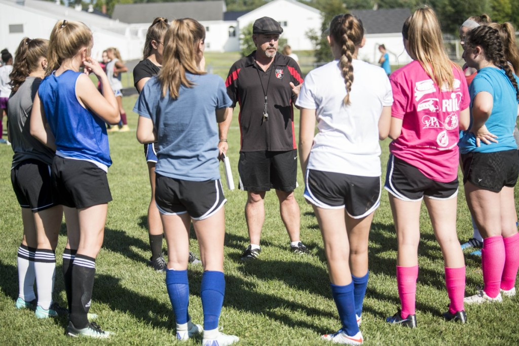 Mike Falla, center, new head coach of the Erskine Academy girls soccer team, talks to his players during practice last week in South China.