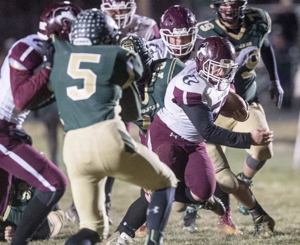 Maine Central Institute's Seth Bussell runs through the Mt. Desert Island line during the Class C North championship game last season night in Bar Harbor. The Huskies open their defense of their title at Leavitt on Friday night.