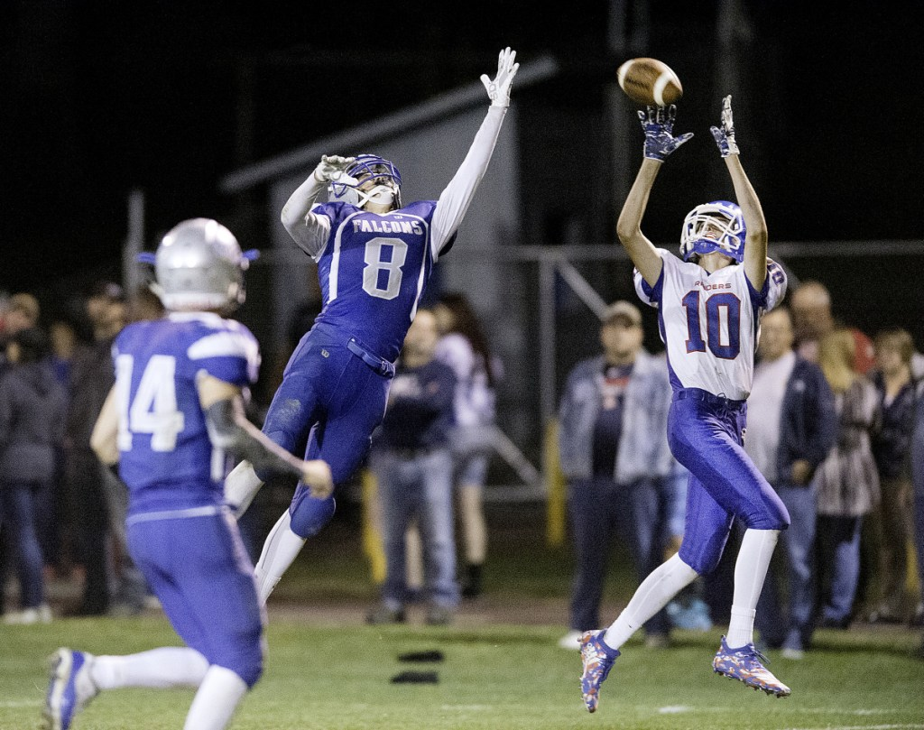 Sun Journal photo by Daryn Slover   Liam Rodrigue of Oak Hill hauls in a 35-yard touchdown pass over Keegan Davis of Mountain Valley during the second quarter in Rumford on Friday.