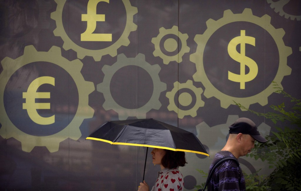 People walk past a mural displaying world currency symbols on the outside of a bank in Beijing. Washington has invited Beijing to hold new talks on their escalating tariff dispute, China said Thursday.