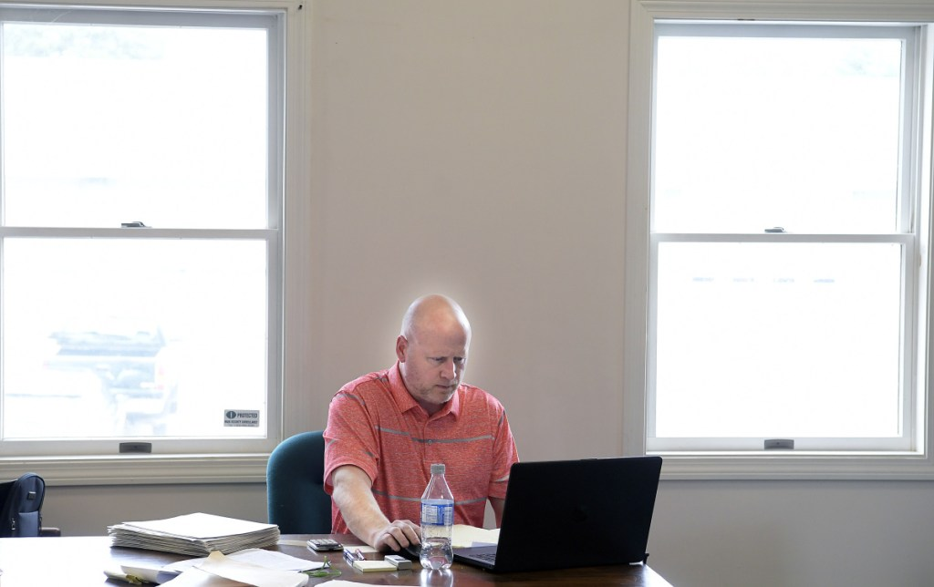 Assessor's Agent Ellery Bane reconciles paper and computer files at the Litchfield town office Thursday.