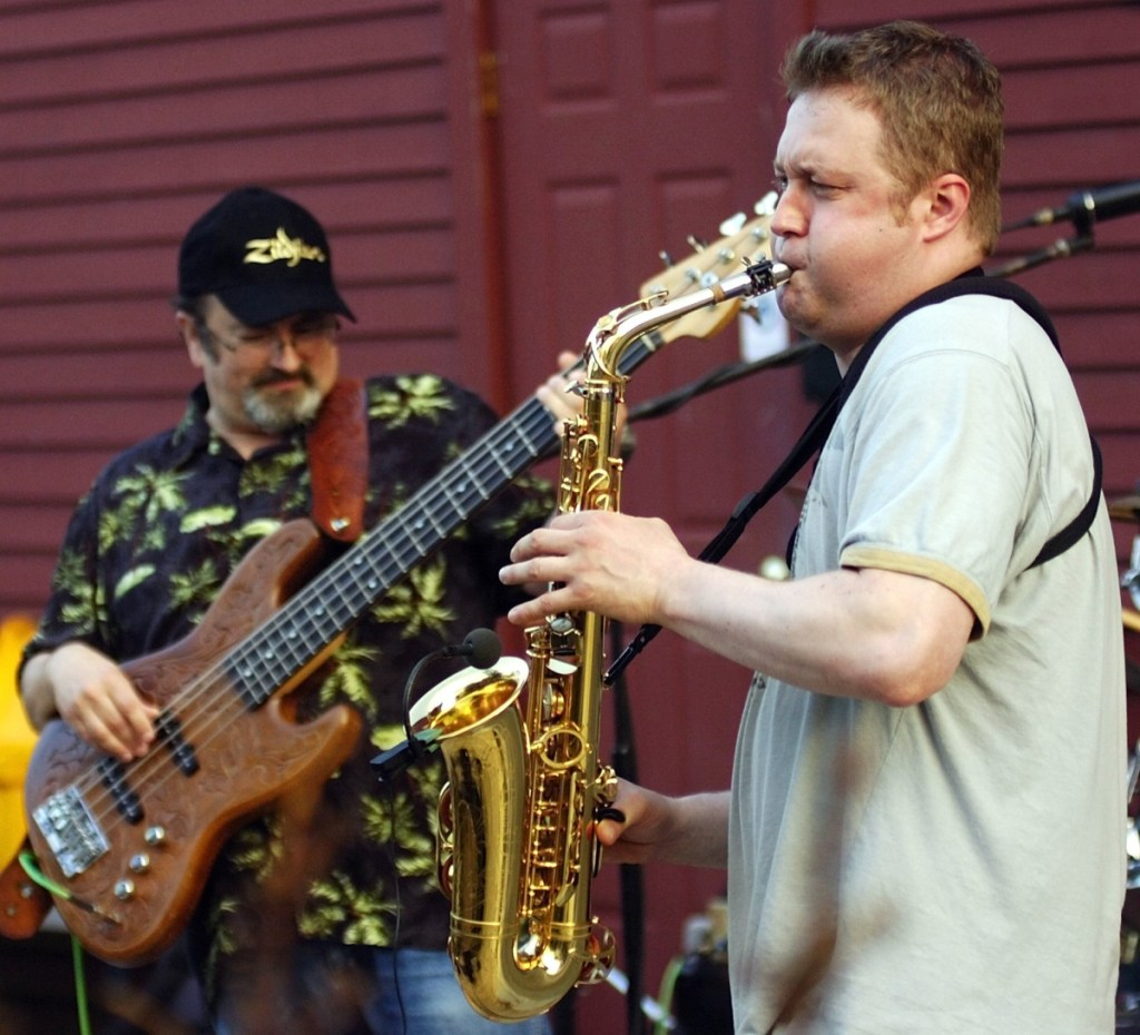 David Thibodeau, left, plays bass while Darren Whitney blows a saxophone solo as their group R&B 3D plays July 28, 2009, on the bandstand at the corner of Water and Winthrop Streets in Hallowell.