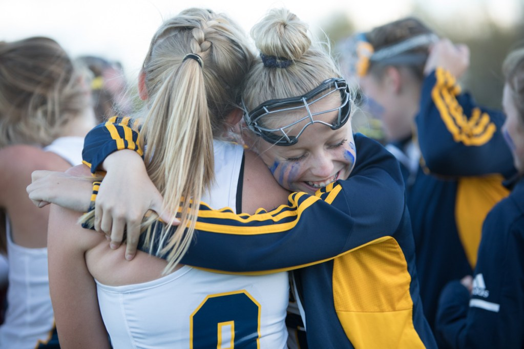 Mt. Blue's Farrah Ballou, right, hugs Bailey Levesque after the Cougars defeated Cony in a Class A North semifinal game Saturday afternoon in Farmington.