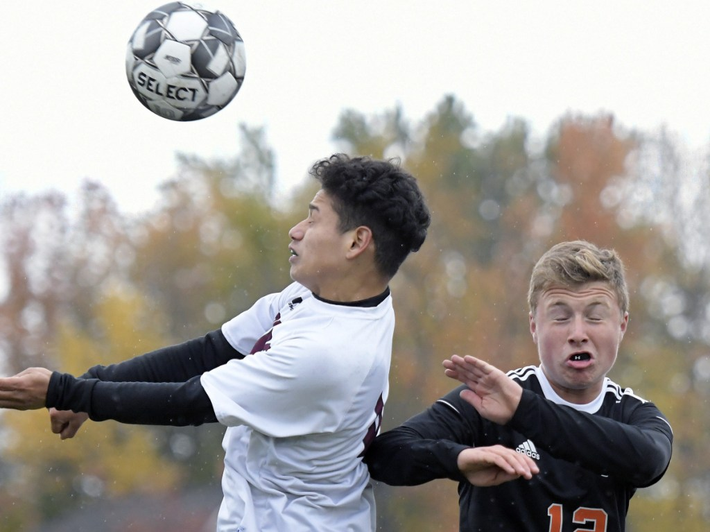 Gardiner's Isaac Gammon, right, heads the ball away from Washington's David Flores during a Class B North quarterfinal game Tuesday in Gardiner.