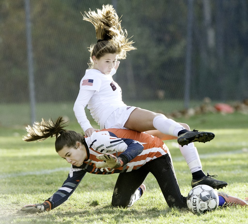 Greely's Logan Pray rolls over Oak Hill goalkeeper Paige Gonya after Gonya made a second in a Class B South quarterfinal game in Wales.