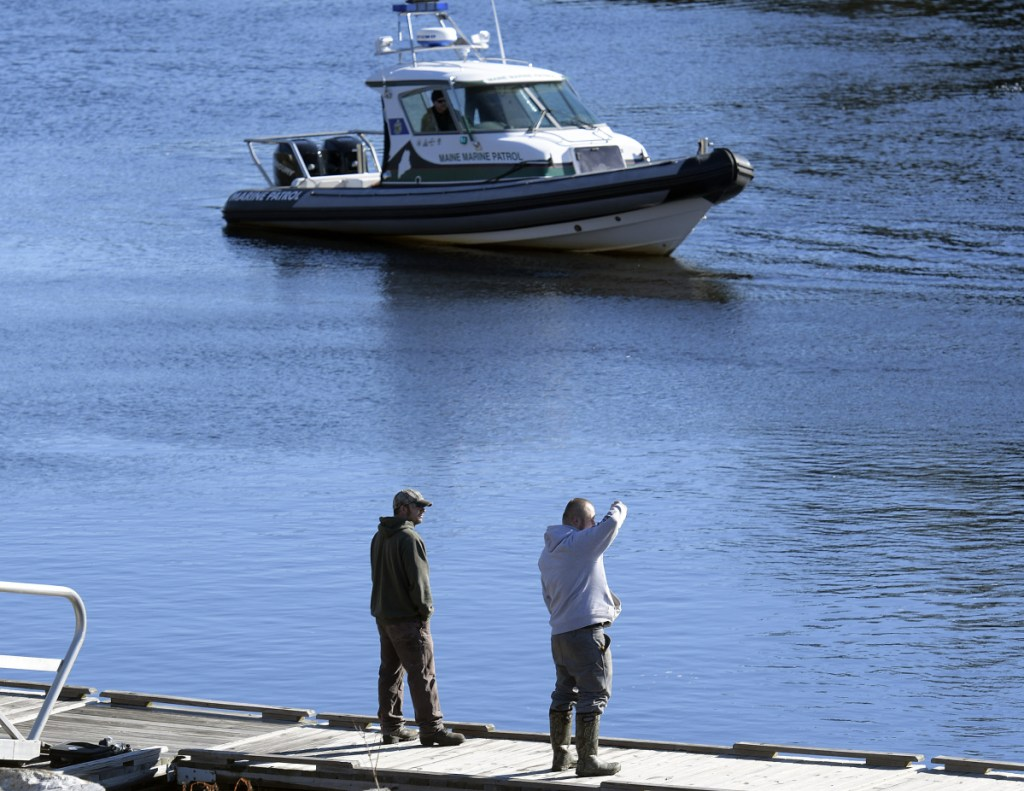 Friends and relatives watch Friday as the Marine Patrol searches the Kennebec River in Richmond for Mark Johnston, 64. Authorities were searching by air, on the water and diving after Johnston disappeared Thursday night. They found a body Friday, but the person's identity was not confirmed immediately.