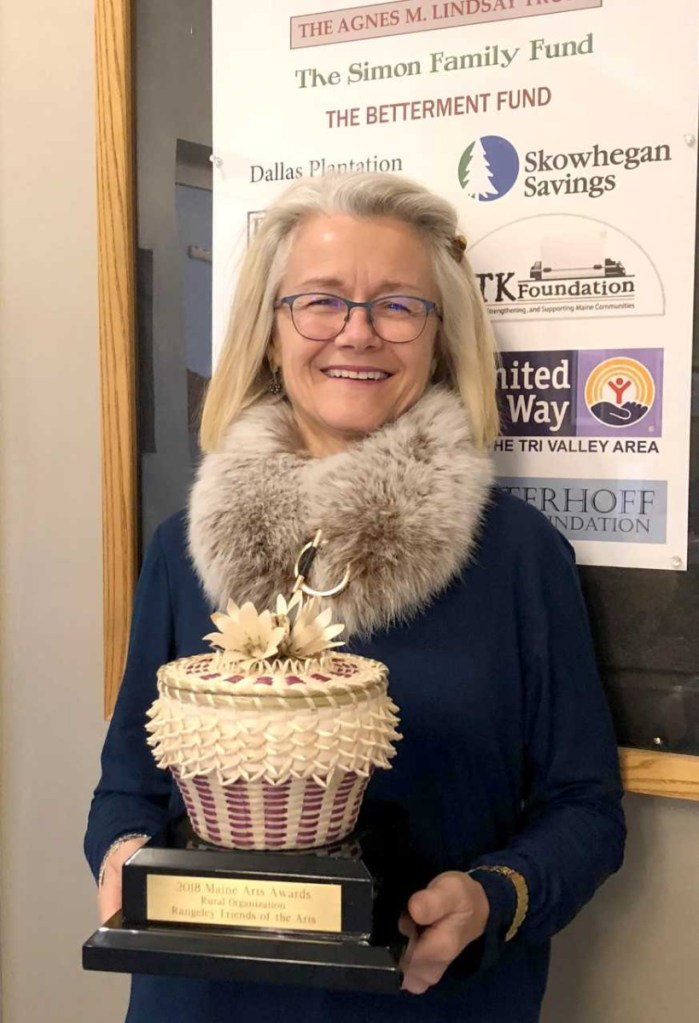 Val Zapolsky, President of the Rangeley Friends of the Arts, displays the hand-crafted ash basket received as the award for being named the Rural Arts Organization of 2018 by the Maine Arts Commission.