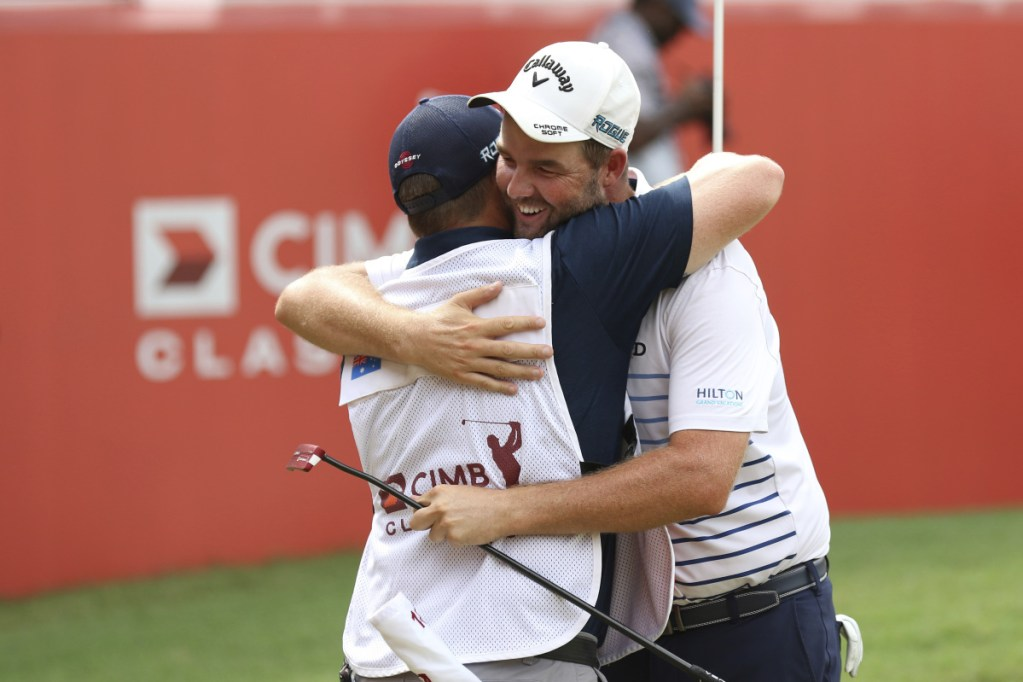 Marc Leishman of Australia celebrates with his caddie Sunday after winning the CIMB Classic golf tournament in Kuala Lumpur, Malaysia. It was Leishman's fourth victory on the PGA Tour.