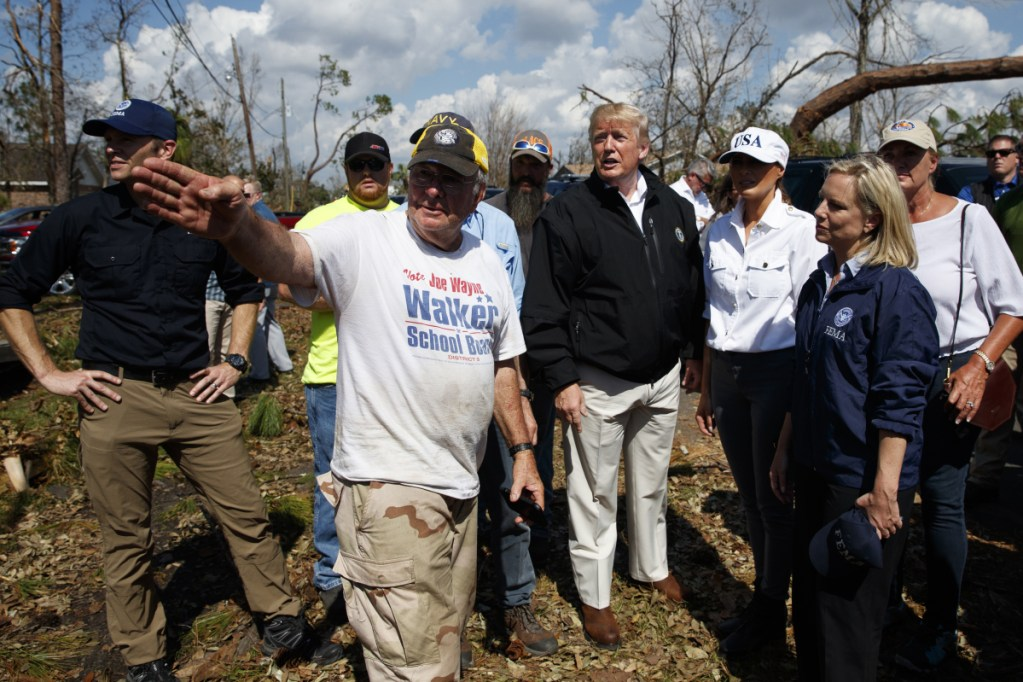 President Trump and Melania Trump tour a neighborhood affected by Hurricane Michael on Monday in Lynn Haven, Florida. Homeland Security Secretary Kirstjen Nielsen is front right.  (AP Photo/)