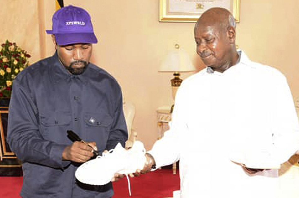 """Kanye West autographs a pair of his sneakers Monday as a gift to Uganda's President Yoweri Museveni at the State House in Entebbe, Uganda. Museveni said he and West held """"fruitful discussions"""" about promoting tourism and arts in the East African nation in which the rapper is said to be recording music in a tent."""