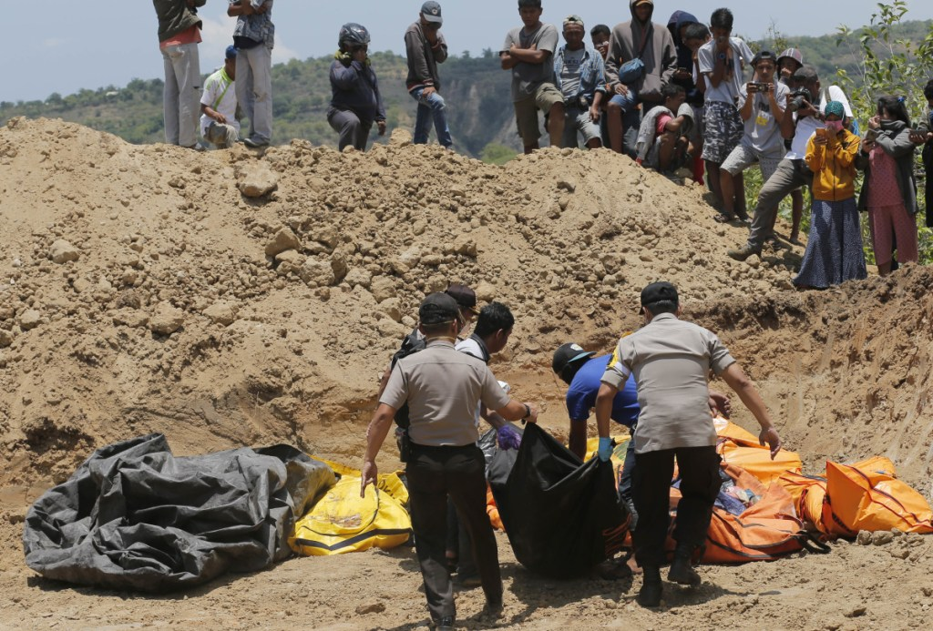 Rescue teams carry the bodies of victims to a mass grave following the major earthquake and tsunami in Palu, Central Sulawesi, Indonesia. Associated Press/Tatan SyuflanaFile