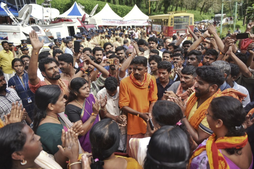Protesters who are opposed to allowing women of menstruating age from entering the Sabarimala temple chant devotional hymns as they gather at Nilackal, a base camp on way to the mountain shrine in Kerala, India, Wednesday. The historic mountain shrine, one of the largest Hindu pilgrimage centers in the world is set to open its doors to females of menstruating age following a ruling by the country's top court. Police arrested some protesters when they tried to block the path of some females. (AP Photo)