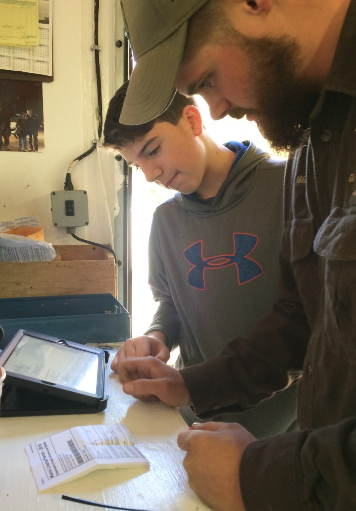 Mike Reynolds, a meat cutter at LaFlamme Custom Meatcutters in Arundel, tags Matt Gonneville's deer using the state's new computerized tagging system.