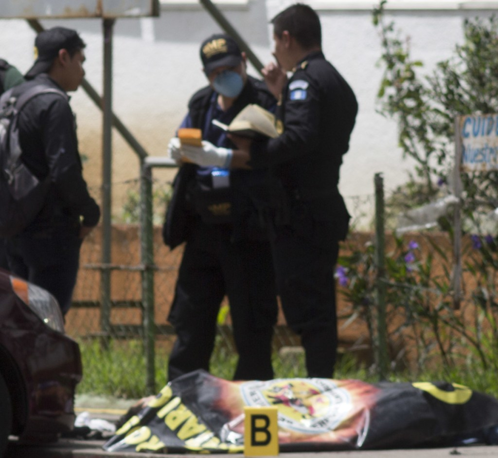Police in Guatemala City investigate the murder of a guard outside a hospital in 2017. Violence is a prime motivator for many of the migrants heading for the U.S.