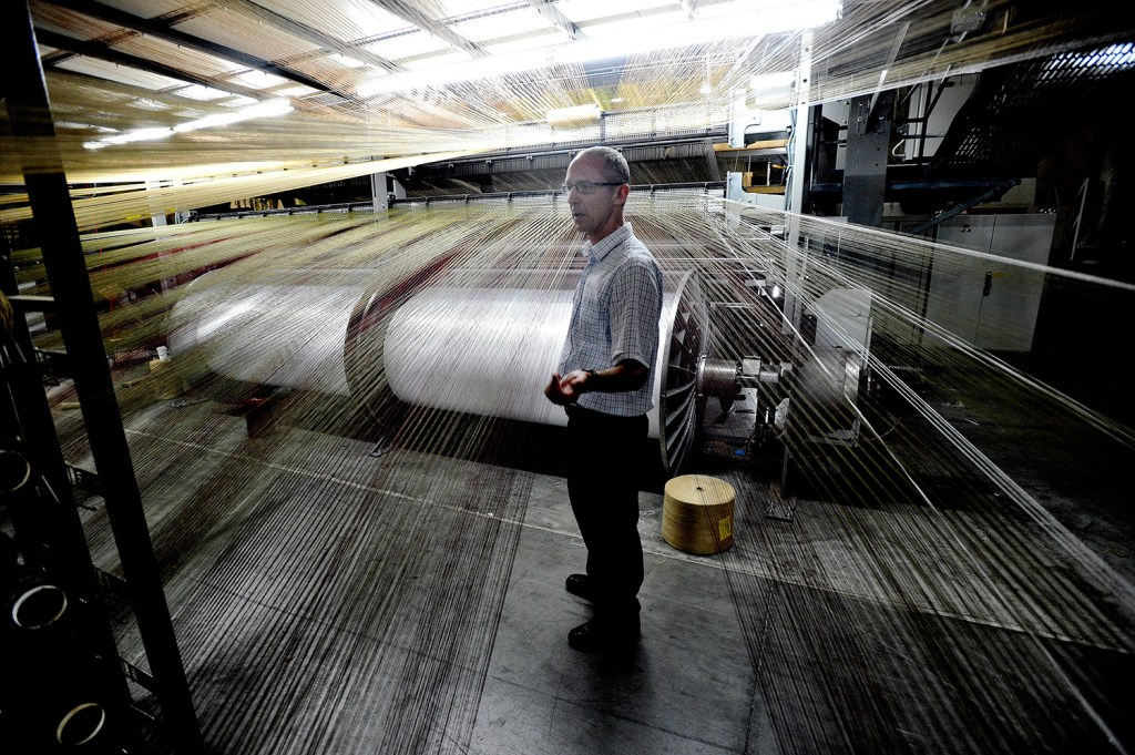 Johan Moulin, president of Flemish Master Weavers in Sanford, stands near one of the company's looms. He said the company is the only U.S. rug manufacturer that lacks its own yarn-making operation.
