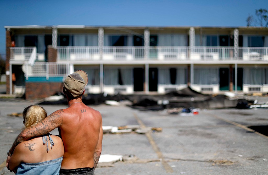 Residents line up for food from the Red Cross outside a damaged motel Tuesday in Panama City, Fla., where many residents continue to live in the aftermath of Hurricane Michael. Some residents rode out the storm and have no place to go even though many of the rooms at the motel are uninhabitable.