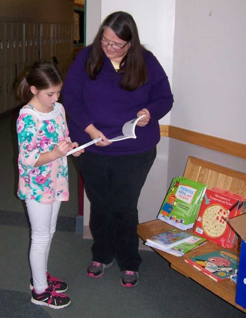 Fourth grader Skylar Thurlow, left, with Title I/Reading Recovery teacher Robin Chase.