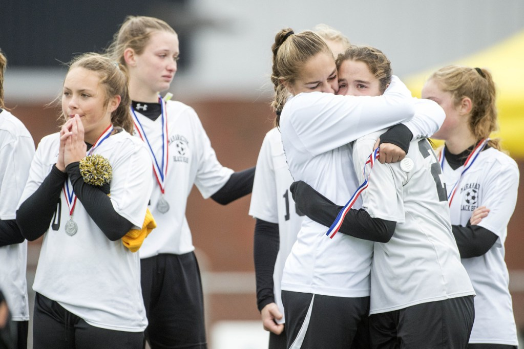 Members of the Maranacook girls soccer team console each other after a 1-0 loss to Fort Kent in the Class C girls state championship game Saturday at Hampden Academy.