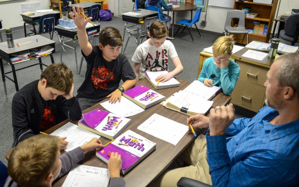 From bottom left, fifth-graders Taisen Pilotte, Alex Reitchel, Wyatt McKenney, Cambell Coutts and Mara Mangin work on mathematics with teacher Adam Hamel on Oct. 18 at Palermo Consolidated School.