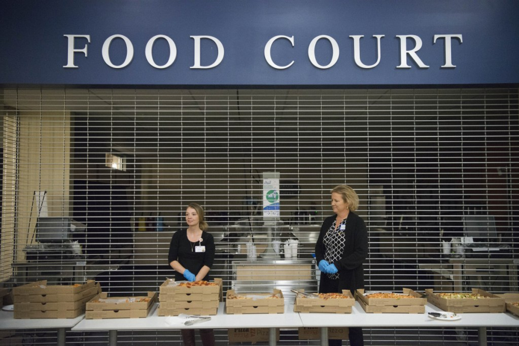 Heather Fellman, left, and Jennifer McCormack, right, wait to hand out pizza for dinner during a break in the community forum on overall health of Franklin County at Mt. Blue High School in Farmington on Oct. 25.