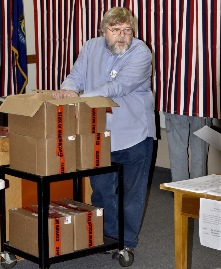 "Staff photo by David Leaming Skowhegan election warden David James keeps his hand on boxes of official state ballots during voting Tuesday at the Skowhegan Municipal Building. ""We're using a lot of these,"" James said, referring to ballots and citing a steady turnout of voters."