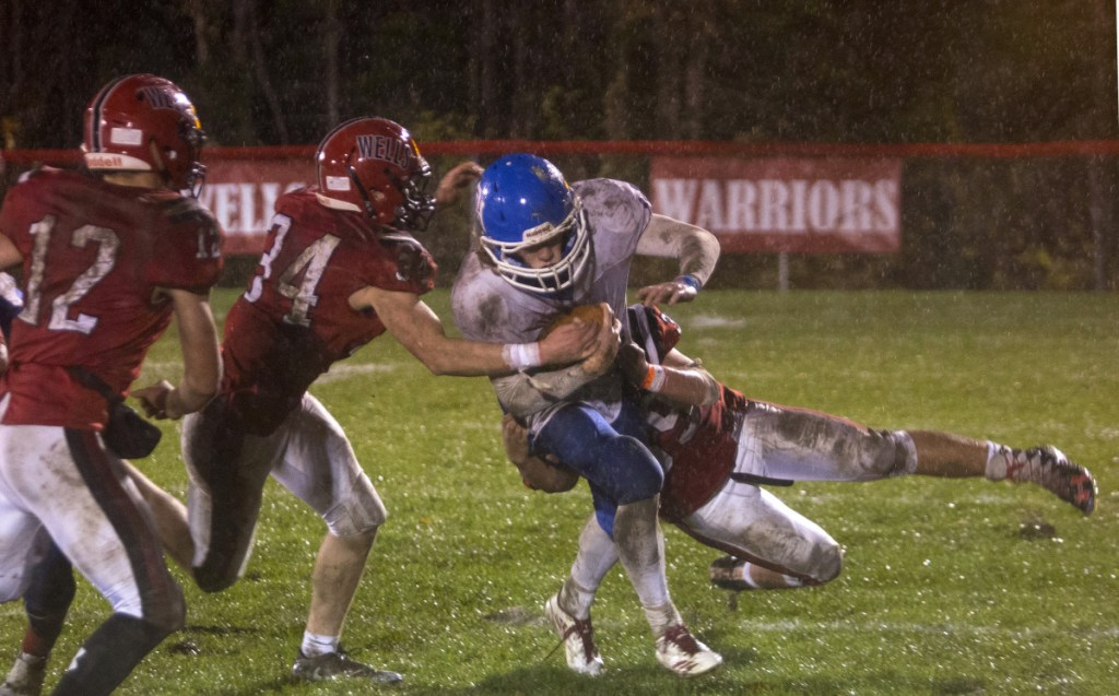 Oak Hill's Samuel Lindsay (14) is taken down by two Wells players during the first half of the Class D South football final on Friday night in Wells.