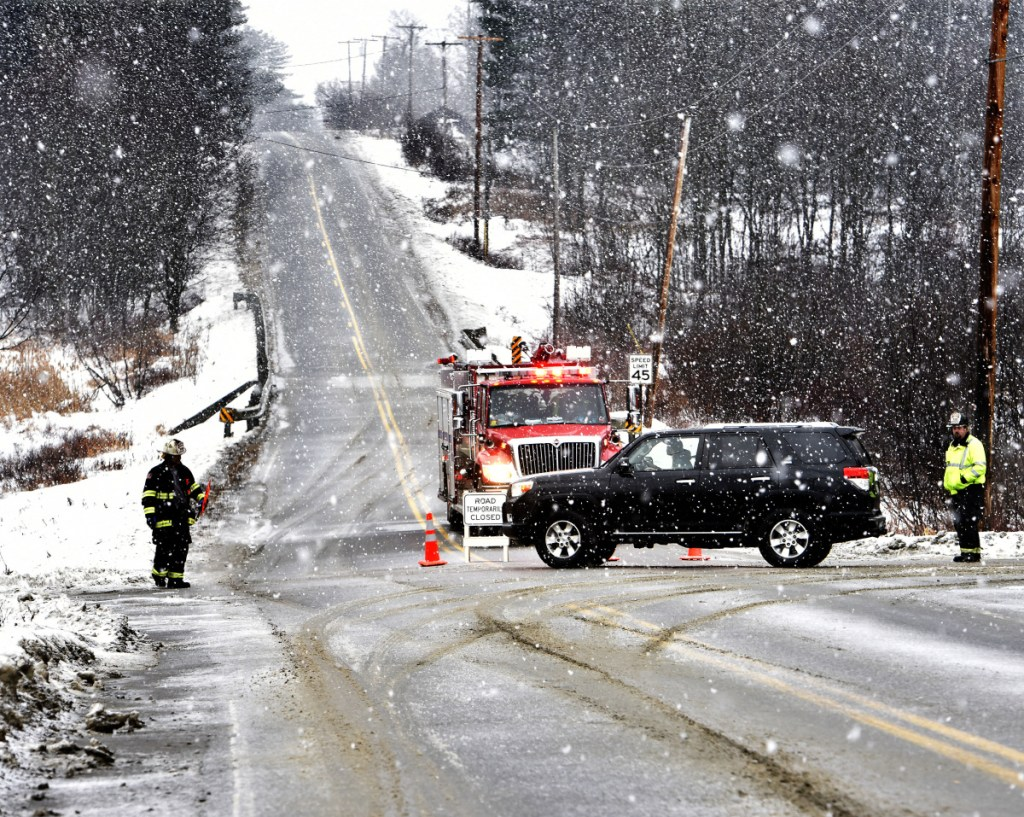 Firefighters from Madison detour traffic at the intersection of Route 43 and Molunkus Road in Cornville as police investigate a fatal accident on Route 43 as snow fell on Sunday.