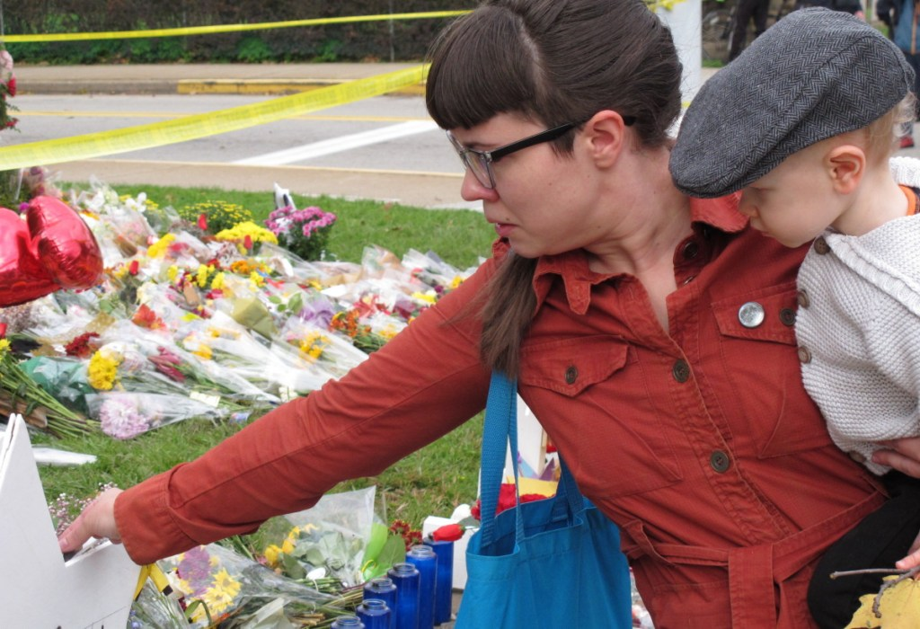 Kathleen Fuller, holding her son Garrick, places a stone on a star of David at a memorial in front of Tree of Life synagogue in Pittsburgh on Wednesday. The massacre underscores the dilemma of law enforcement in assessing the risk of people making online rants when social media is so ubiquitous.