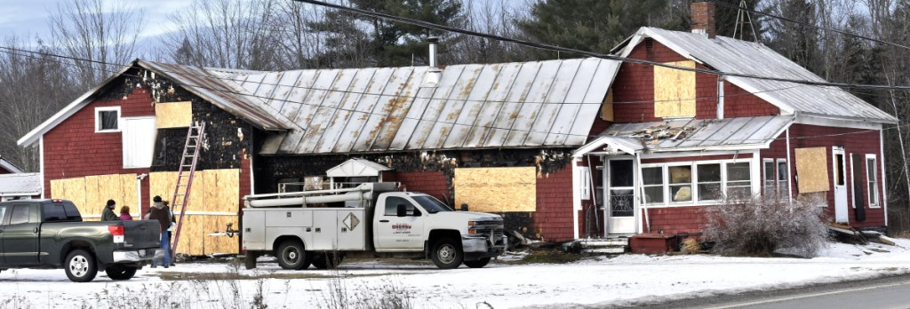 People assemble at left to survey damage to the home on Main Street in Pittsfield on Sunday. Fire caused extensive damage on Saturday.