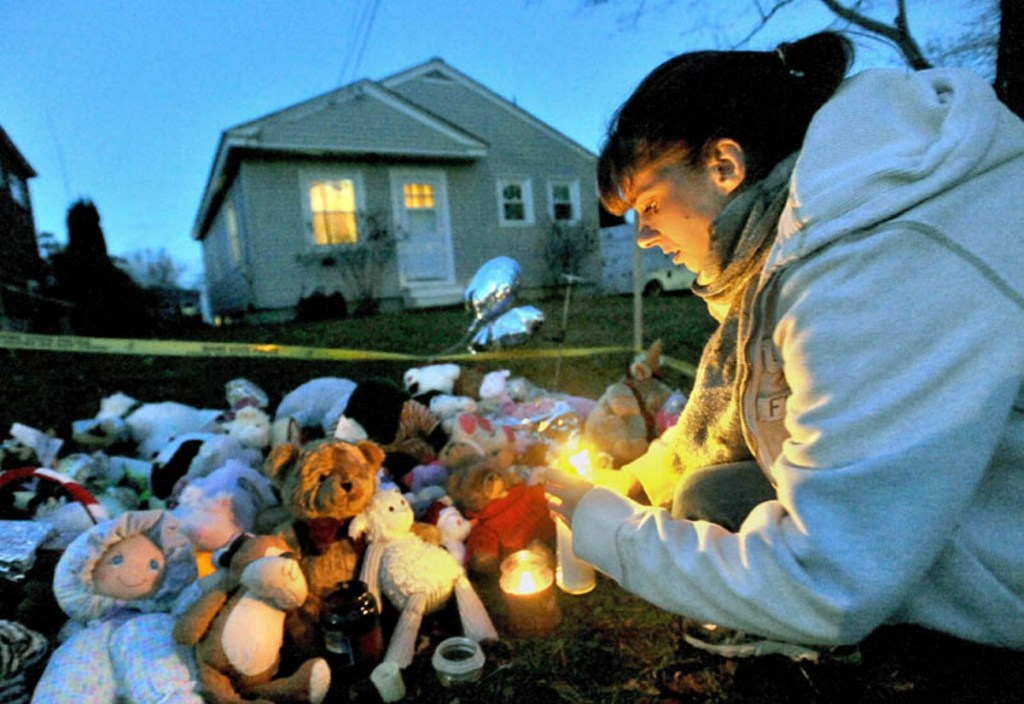 Tara True, of Winslow, lights candles at the ever-growing teddy bear shrine in front of the Violette Avenue residence in Waterville where 20-month-old Ayla Reynolds was last seen in December 2011.