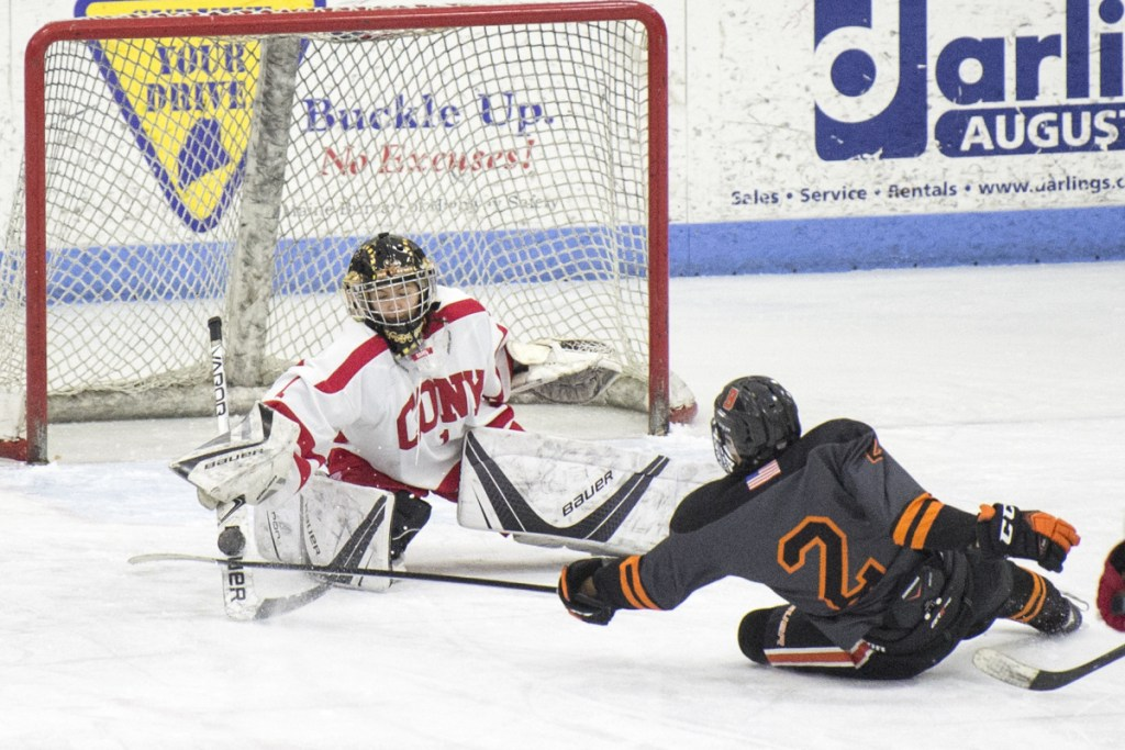 Cony goalie Matty Shea makes a save on a shot by Brunswick's Nick Levesque on Saturday at the Camden Nation Bank Ice Vault in Hallowell.
