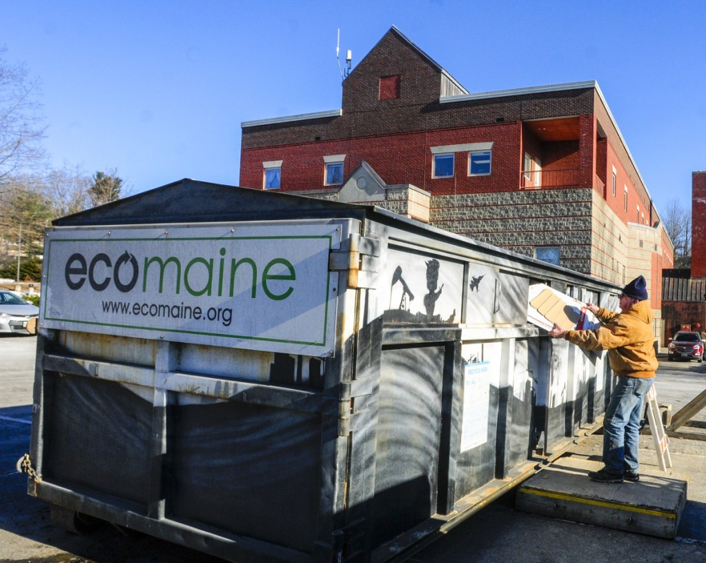 Les Mason puts cardboard into an ecomaine recycling rolloff container Dec. 13 at the Augusta police station. The City Council voted Thursday to remove the bin from that site, as well as the one at Augusta City Center.