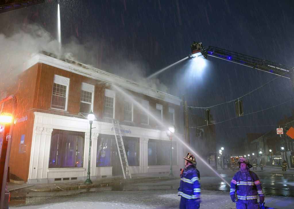 Dozens of firefighters struggle Friday to contain a fire at a building in downtown Gardiner. The blaze was reported just after 3 a.m. at the former bank building at the corner of Church and Water Street.