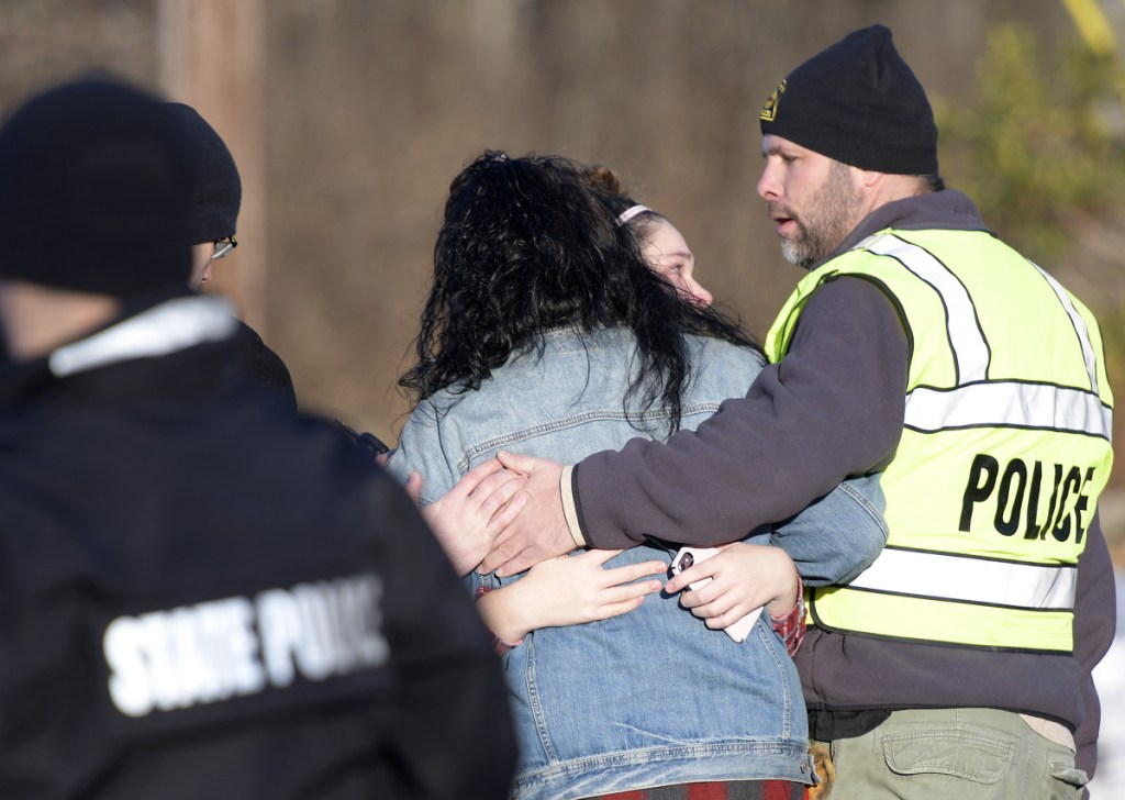 Richmond Police Chief Scott MacMaster comforts relatives of two people found dead Saturday.