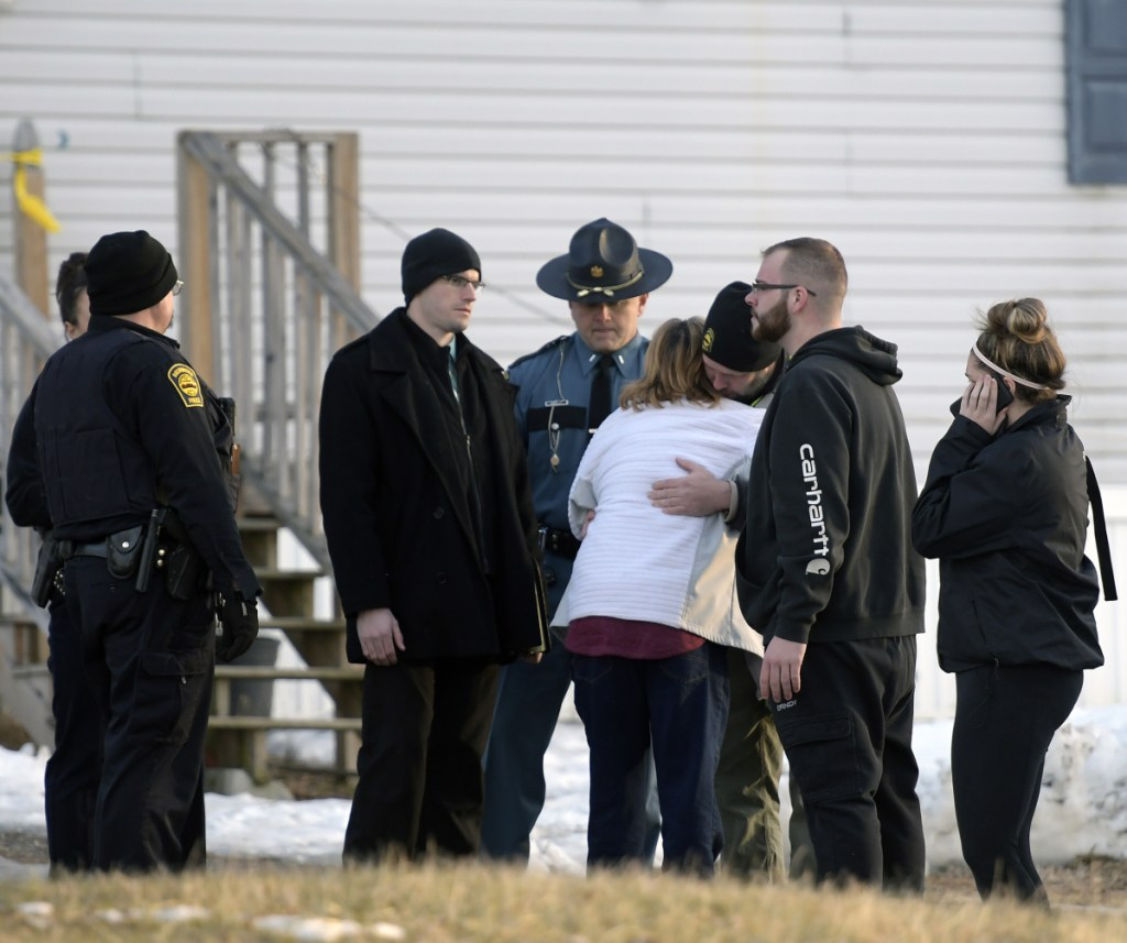 "Richmond Police Chief Scott MacMaster comforts relatives of two people found dead Saturday in a residence on Post Road in Richmond. Police said the deaths were ""not natural"" but there is no threat."