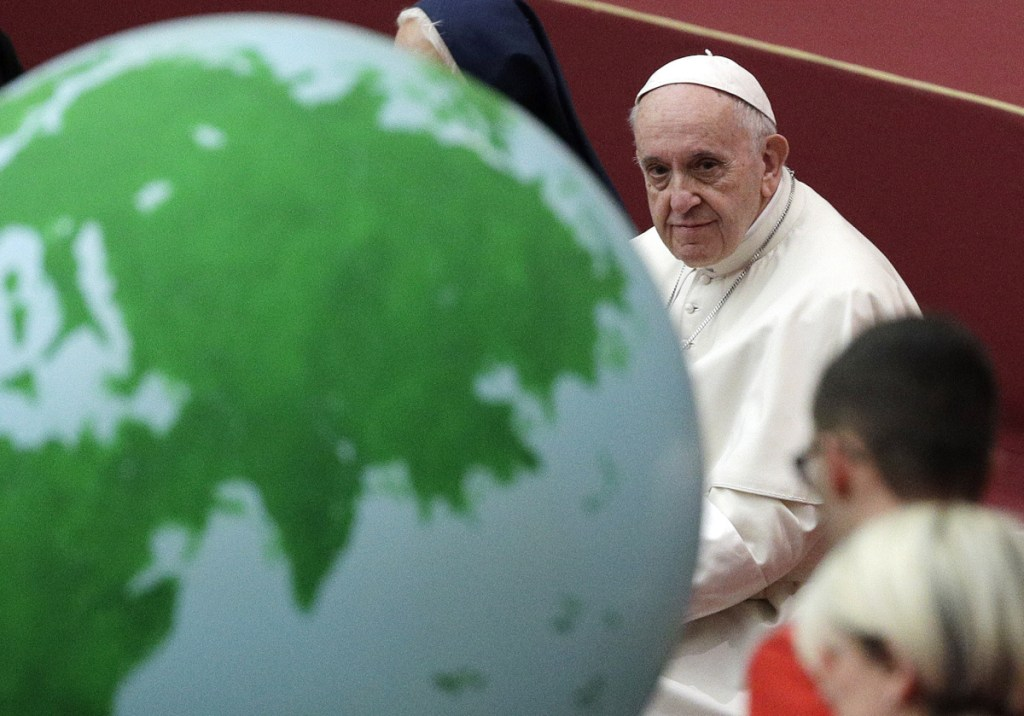 Pope Francis holds an audience with families from a Vatican charity that helps mothers and children in need, at the Vatican on Sunday, the eve of his 82nd birthday. The globe adorned his cake.