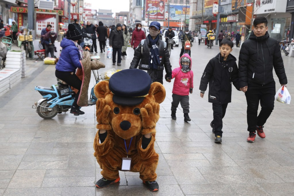 A promoter dressed as a teddy bear rests along a retail street in northern China's Hebei province on Saturday. At least four Chinese cities and one county have restricted Christmas celebrations this year. Churches in another city have been warned to keep minors away from Christmas, and at least 10 schools nationwide have curtailed Christmas on campus, The Associated Press has found.