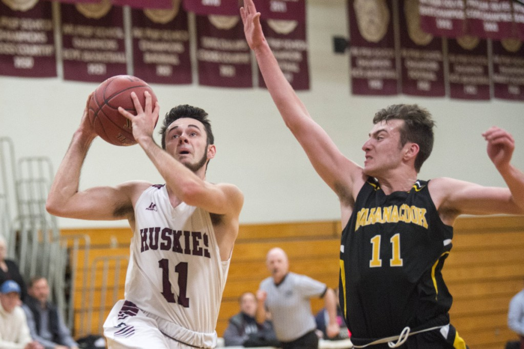 Maine Central Institute's Gavin McCarthur (11) drives to the basket as Maranacook's Garrett Whitten, right, tries to defend Wednesday in Pittsfield.