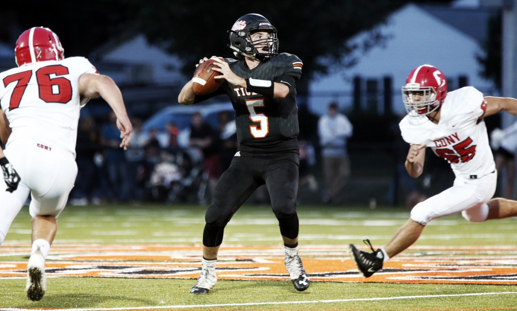 Biddeford quarterback Carter Edgeton feels the pressure from Cony's Nic Mills, left, and Jacob Mills during a game earlier this season.