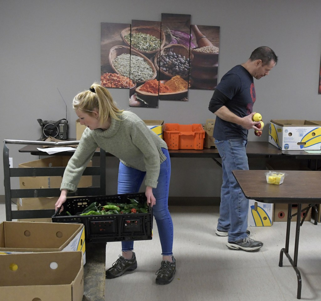 Augusta Food Bank staff members Melissa Shea and Andy Waller collect items for customers Tuesday. Several food security groups in central Maine have opened their doors to federal employees who have gone unpaid since December.