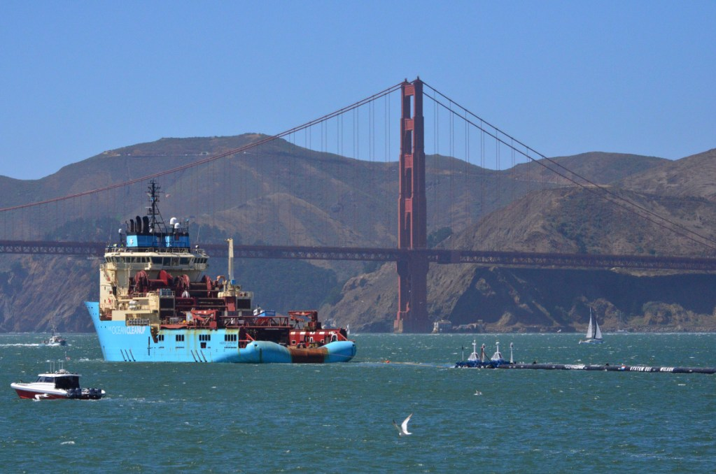 A ship tows Boyan Slat's first buoyant trash-collecting device toward the Golden Gate Bridge in San Francisco en route to a patch of 1.8 trillion pieces of plastic floating in the Pacific Ocean. After it arrived, the boom initially didn't pick up much material because it was moving slower than the plastic, allowing the trash to float away. Then the boom broke apart under constant wind and waves and is now being returned to shore for repairs.