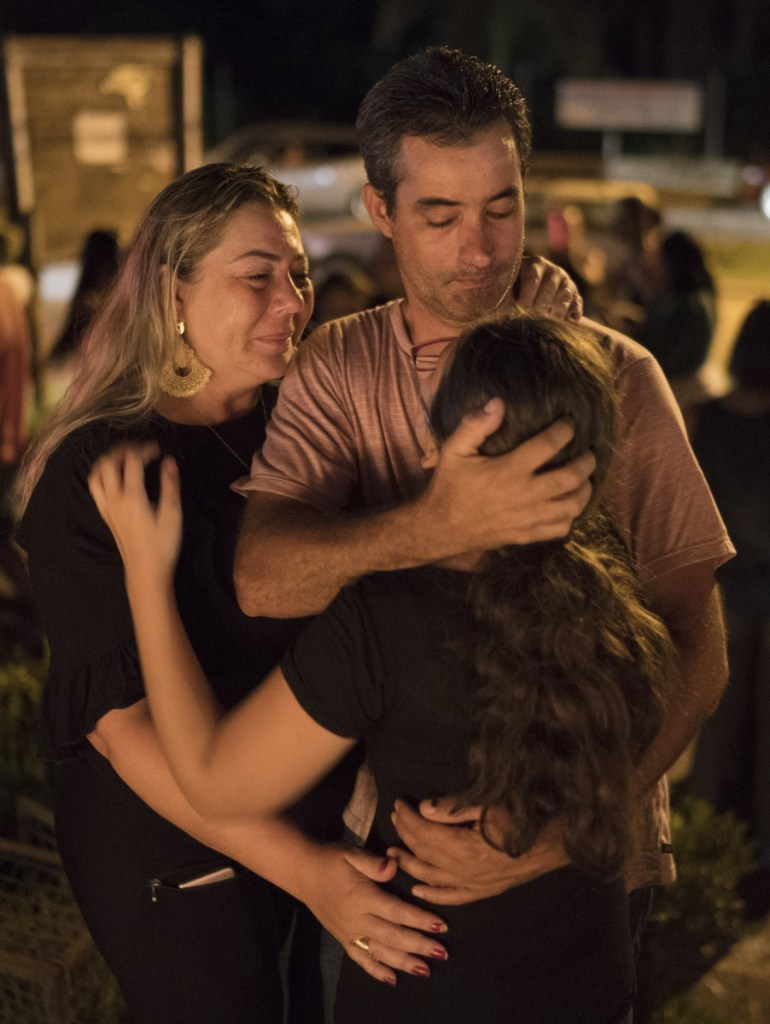 A family embraces during a vigil for the dam victims in Brumadinho, Brazil, Tuesday. Authorities arrested five people Tuesday in connection with the collapse of the dam, while the death toll rose to at least 84 and the carcasses of fish floated along the banks of a river downstream that an indigenous community depends on for food and water.