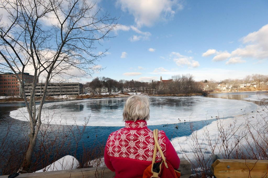 Pat Mahoney of Gorham checks out the giant disk of ice on the Presumpscot River in Westbrook on Wednesday, even though it had lodged against the riverbank and stopped spinning.
