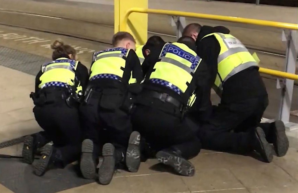 Police restrain a man accused of stabbing three people at Victoria Station in Manchester, England, late Monday.