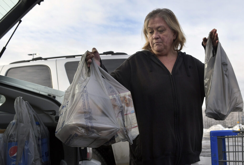 Earlinda Nirza, of Augusta, gathers plastic bags full of groceries Jan. 10 after shopping at Walmart in Augusta.